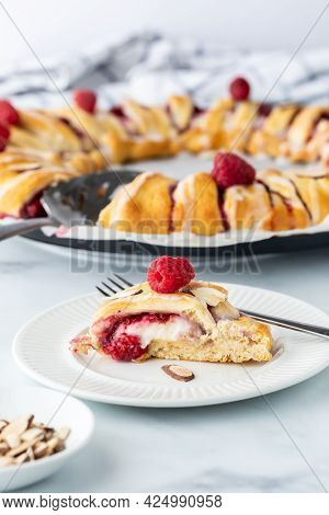 Close Up View Of A Slice From A Raspberry Crescent Ring With The Full Ring In Behind.