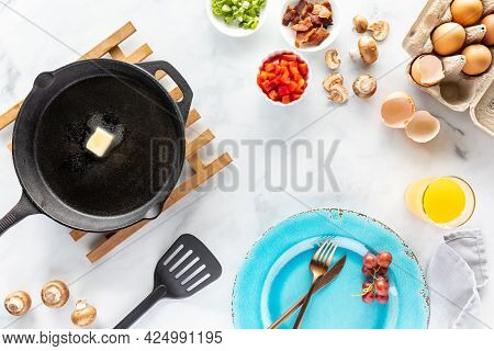 Top Down View Of All The Ingredients Used To Make A Homemade Omelette And A Frypan With Melting Butt