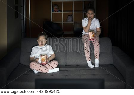 Two Sister Girls Are Watching A Tv Show On Tv With Interest On The Couch In A Dark Room In The Eveni