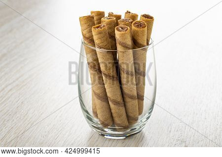 Brown Striped Wafer Rolls With Chocolate Filling In Transparent Drinking Glass On Wooden Table