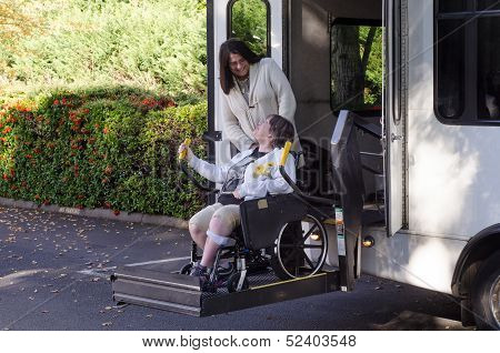 A woman in a wheelchair is helped off a van using a chair lift. poster