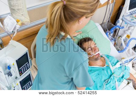 High angle view of mid adult nurse adjusting patient's pillow in hospital room