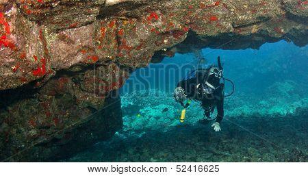 Diver Exploring A Lava Arch In Hawaii