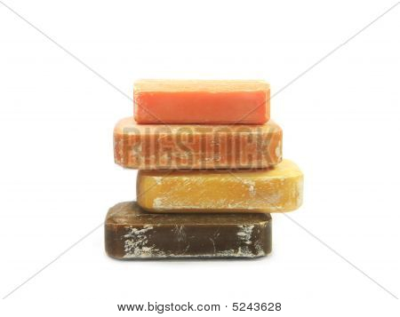 Tower of 4 colorful bars of handmade natural soap isolated on white background. poster