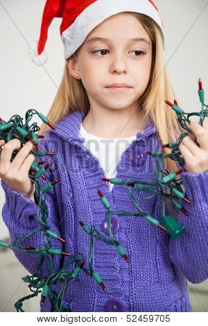 Girl wearing Santa hat looking at fairy lights during Christmas in house