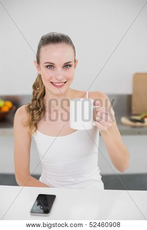 Happy young woman holding a mug looking at camera in the kitchen at home