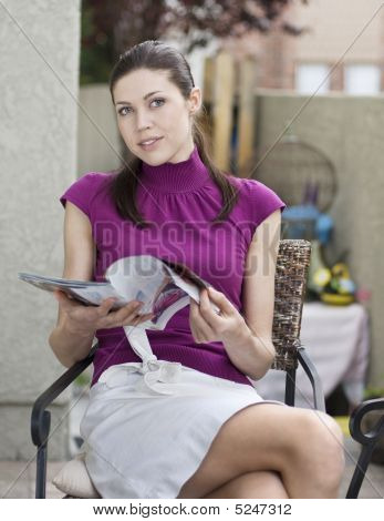 Beautiful Young Woman Reading A Magazine