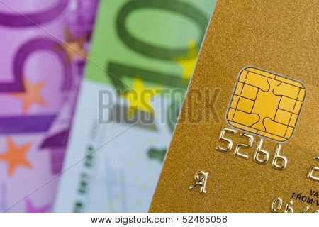 a gold credit card and euro banknotes. symbolic photo for cashless transactions and status symbols.