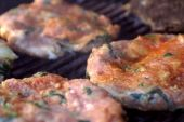 Well seasoned Chicken Florentine Hamburgers cooking outdoors on a hot charcoal grill. ** Note: Shallow depth of field poster