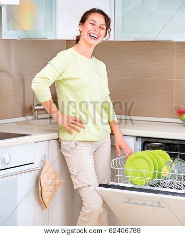 Dishwasher. Happy Young woman in the Kitchen doing Housework. Dishwasher Machine, dishwashing. Wash-up. Smiling Girl using dishwasher machine