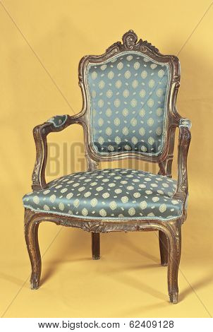 Louis XV armchair on yellow ocher background