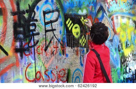 Person Adding Grafitti To The John Lennon Wall