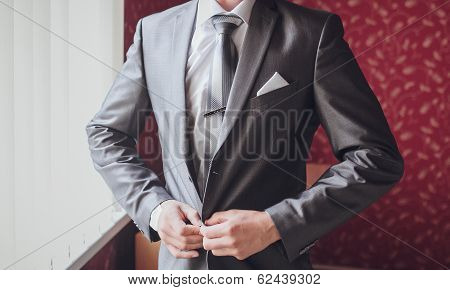 groom getting ready in suit