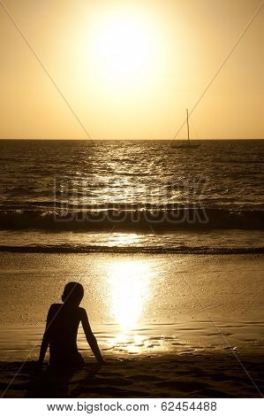 Boy watches a sailboat at sunset