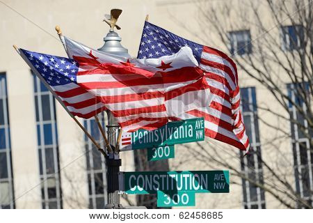 Washington DC, Pennsylvania Avenue and Constitution Avenue junction street signs with DC and United States of America flags on the same post