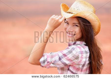 Cowgirl woman smiling happy on american prairie wearing cowboy hat. Beautiful young multiracial Asian Caucasian girl in countryside.