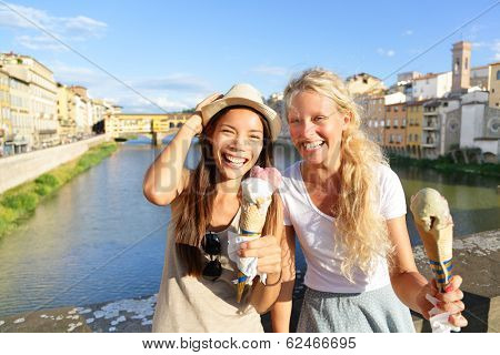 Happy women friends eating ice cream on travel in Florence. Cheerful girlfriends enjoying italian food gelato cone smiling happy by Ponte Vecchio during vacation holidays in Tuscany, Italy, Europe.