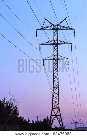 high voltage electricity transmission tower with powerlines and pylons