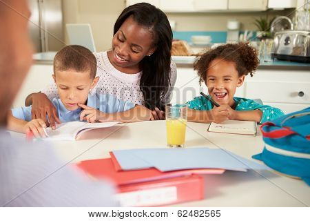Mother Helping Children With Homework At Table