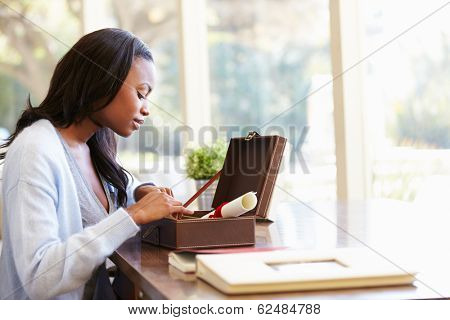 Woman Looking At Document In Keepsake Box On Desk