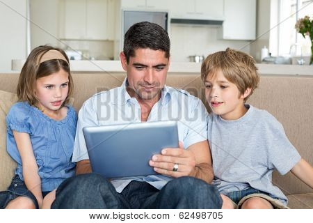 Father teaching to use digital tablet while sitting on sofa at home poster
