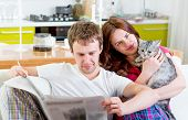 Young married couple in pajamas sitting in the sofa with newspaper and cat at home poster