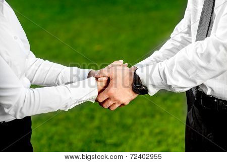 Business couple shaking hands outdoors