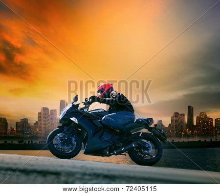 Young Man And Safety Suit Riding Big Motorcycle Against Beautiful Dusky Sky And Urban Scene With Cop