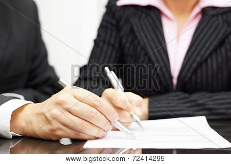 Woman And Man Are Analyzing And Fulfilling Document