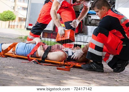 Paramedics giving first aid girl after accident poster