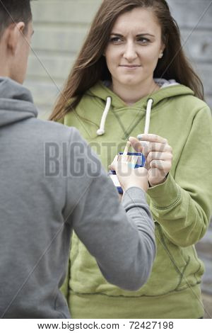 Boy Offering Teenage Girl Cigarette Outdoors
