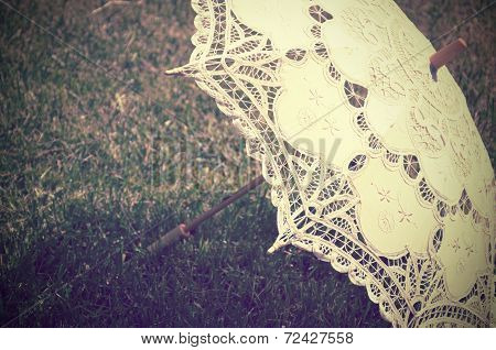 Lacy Parasol On The Grass Close Up. Tinted Vintage