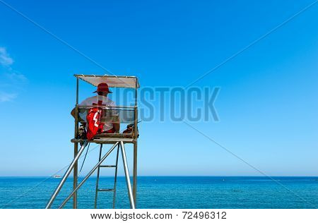 A Lifeguard Sitting On Surveillance Tower