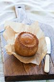 The traditional pork pie with a high contrast background to the rear of the image and selective focus on the top of the pie poster
