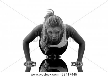 Beautiful woman doing push ups on beach against mirror