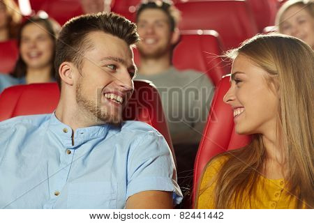 cinema, entertainment and people concept - happy friends watching movie and talking in theater