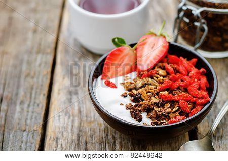 Fresh Breakfast Of Granola, Yogurt, Nuts, Goji Berries And Strawberries