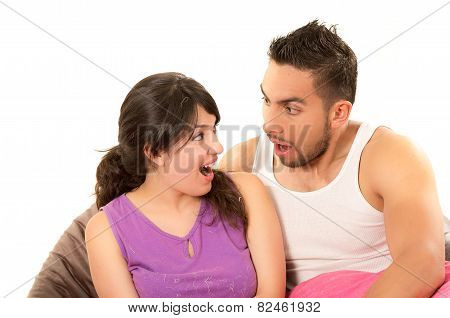 sweet latin couple looking at each other surprised wearing their pijamas