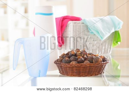 Basket full of soap nuts, natural bio detergent and laundry with bottle and scoop