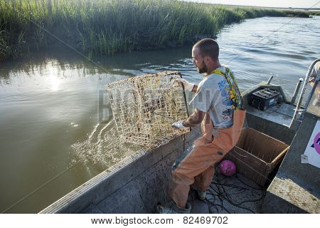 BEAUFORT, SOUTH CAROLINA-MAY 23, 2014: An unidentified commercial fisherman hauls a crab trap onto a boat