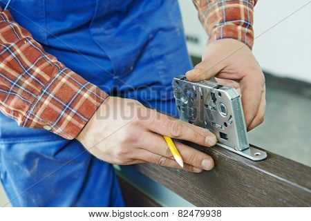 Close-up carpenter hands with doorlock during lock process installation into wood door poster