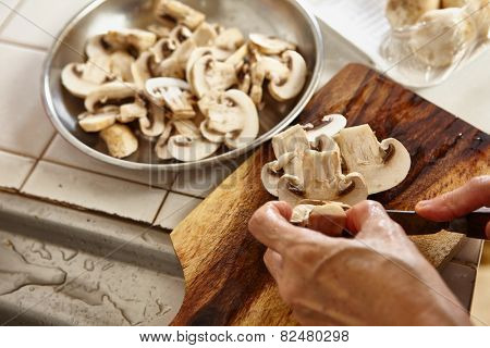 Cutting the mushroom into thin slice as ingredient for mushroom omelette, slight movement blur might be noticeable