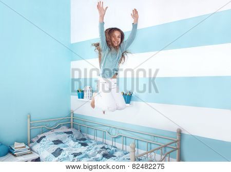 8 years old kid girl jumping on the bed at her room