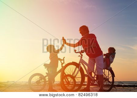 father with kids biking at sunset