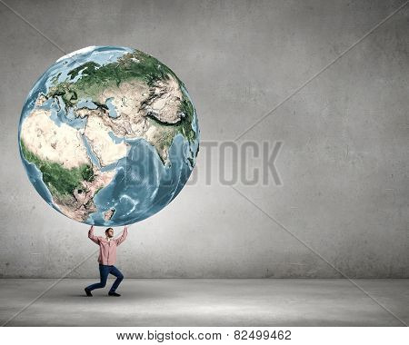 Young man making effort to lift Earth planet above head. Elements of this image are furnished by NASA