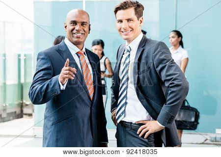 Business team with Asian and Caucasian executives having informal meeting outdoors in front of office