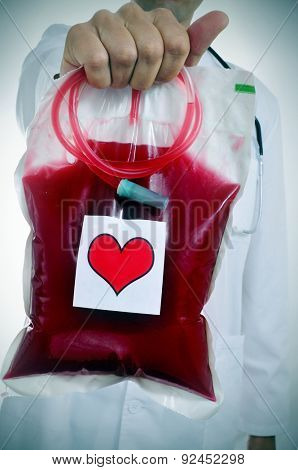closeup of a doctor holding a blood bag with a sticker of a red heart
