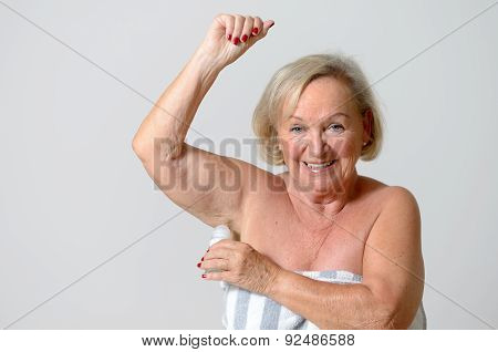 Close up Middle Aged Blond Lady Applying Deodorant on Armpit After Shower While Looking at the Camera Against Light Gray Wall. poster