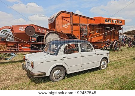 Vintage Car Fiat 1100 Near To An Old Thresher Machine