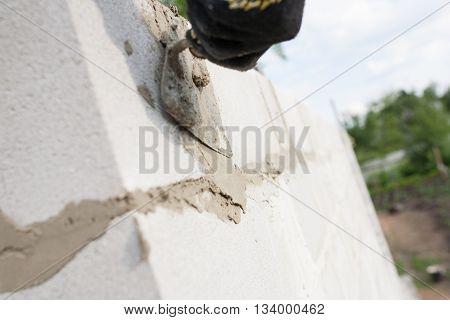 worker aligns with a spatula lay brick cinderblocks.